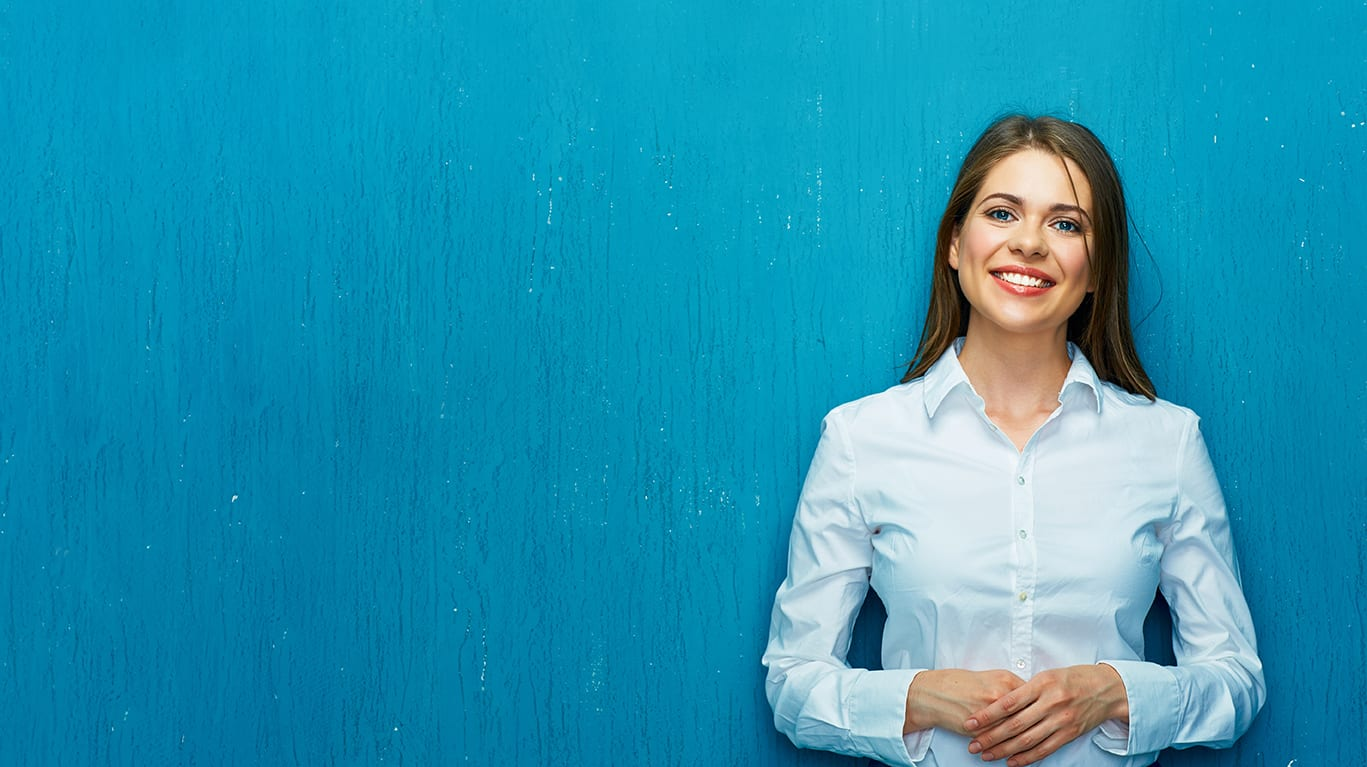 Smiling young woman in blue button-up shirt standing in front of solid blue wall